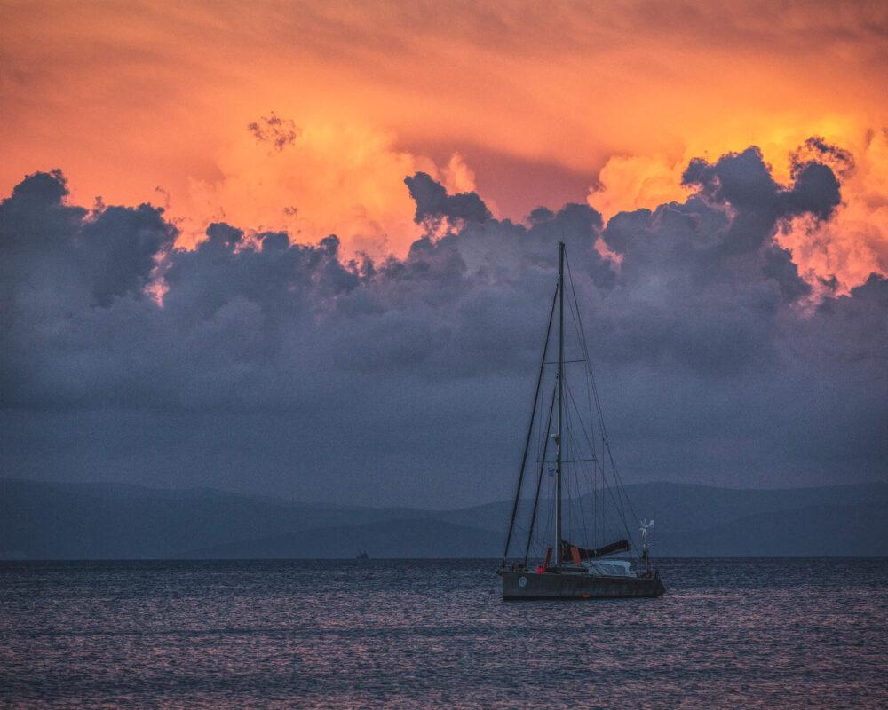 Feuerroter Himmel mit beeindruckenden Wolken über dem Meer mit Segelboot im Vordergrund