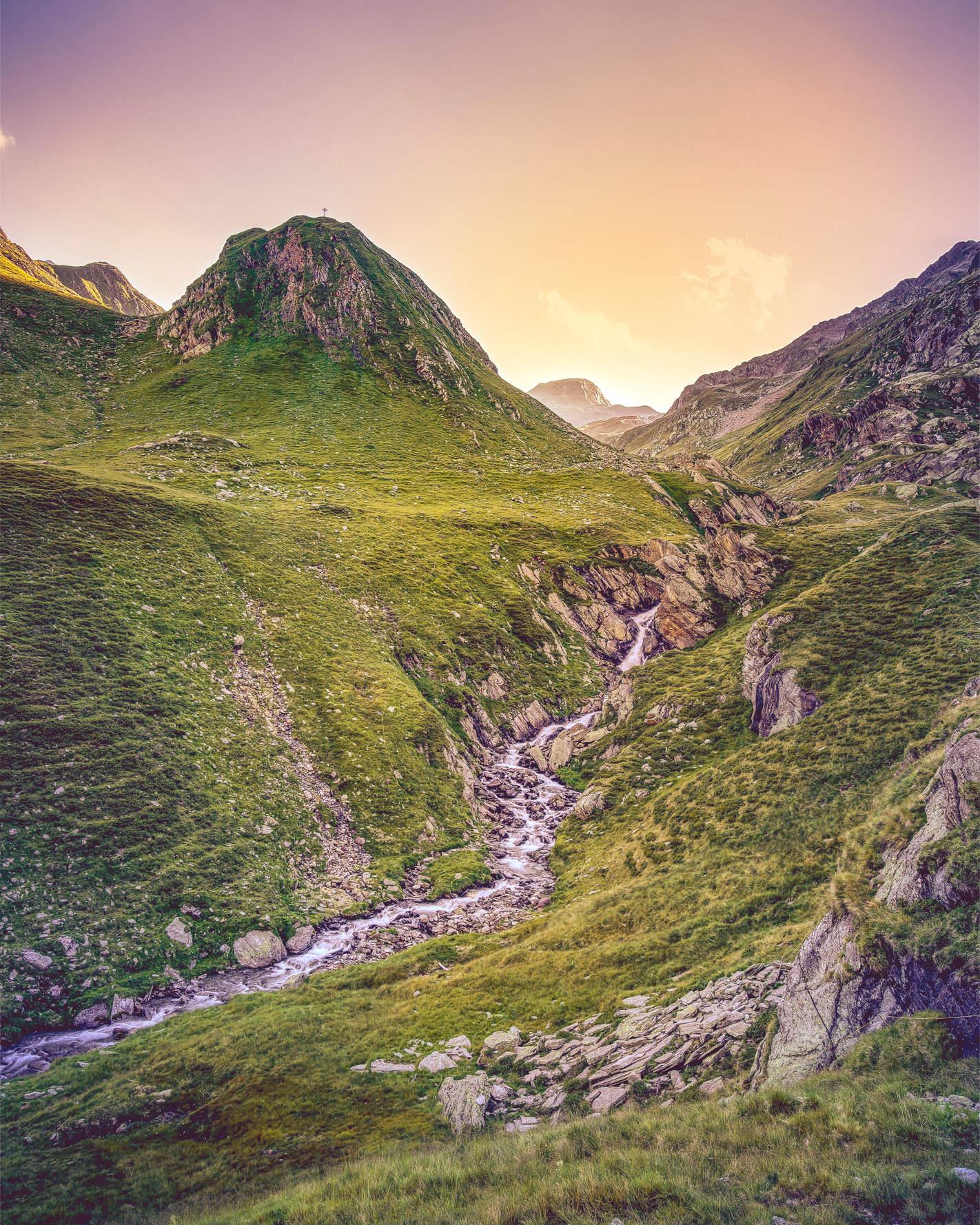 Golden erleuchtetes Tal mit Bach und Berggipfeln am Abend in den Alpen Südtirols