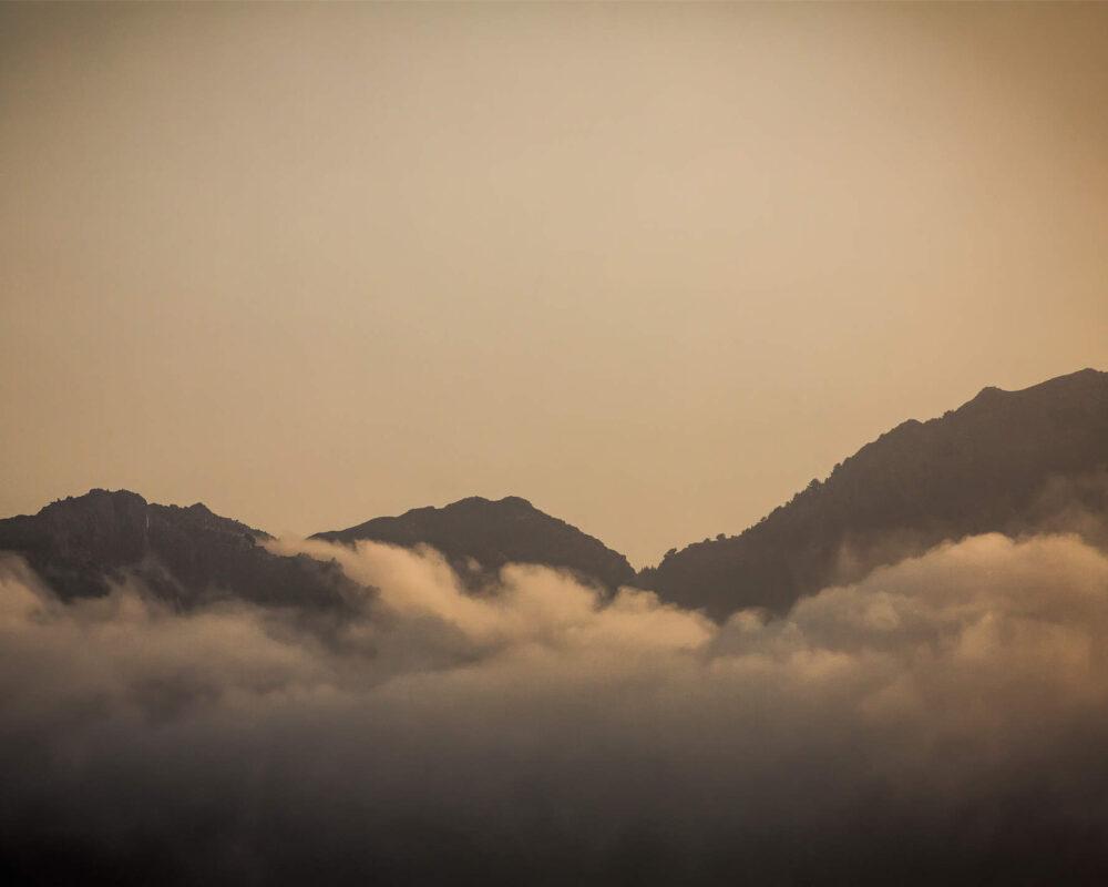 Von Wolken umschlungene Berggipfel im Licht der Morgensonne