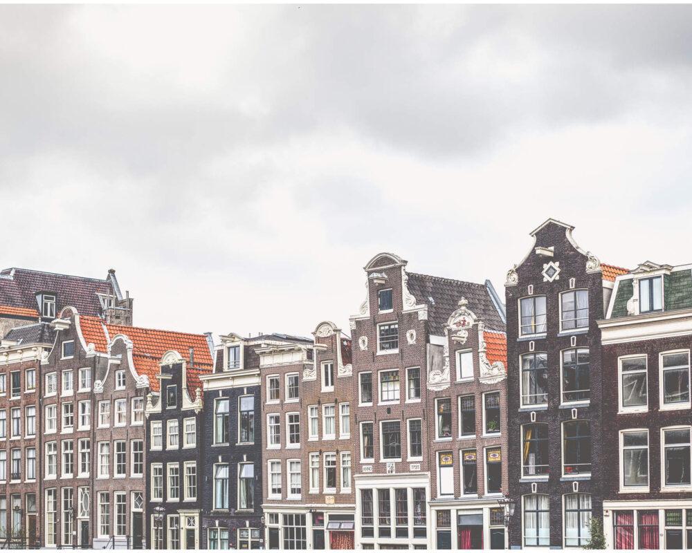 Häuserfronten an den Kanälen Amsterdams mit bedecktem Himmel