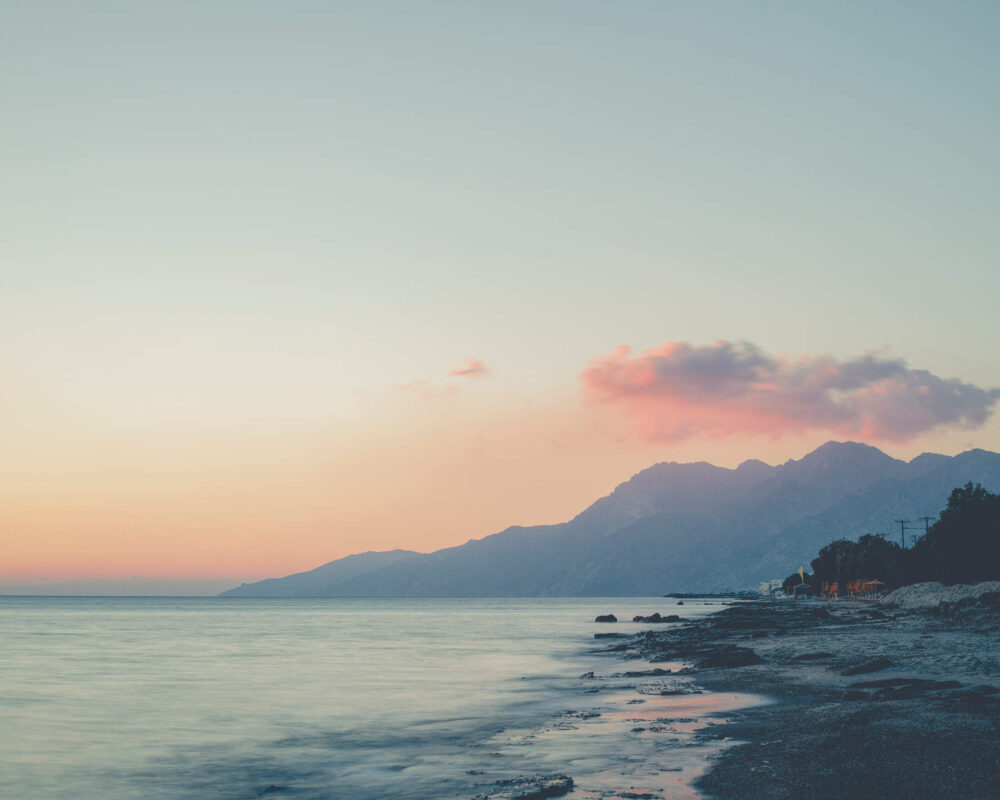 Morgendämmerung am Strand mit türkisem Meer und rosa Himmel