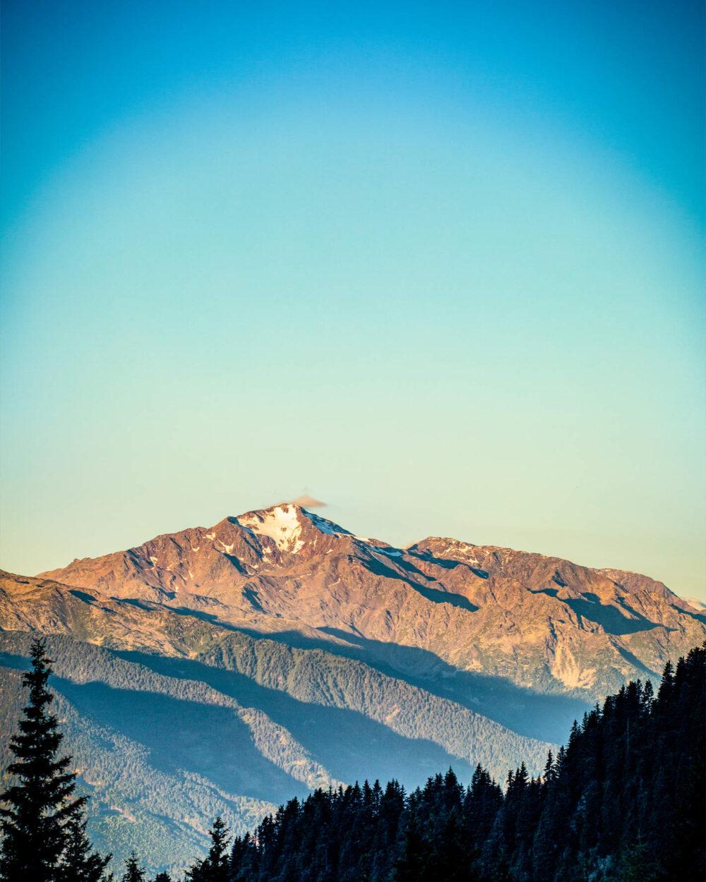 Kleines Wölkchen über Berggipfel im Morgengrauen
