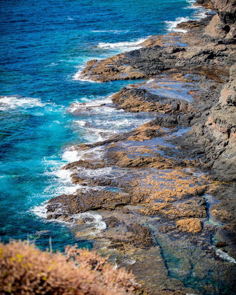 Schwarzer Felsstrand Playa la Caleta mit tiefblauem Atlanik und kräftigen Wellen auf Gran Canaria