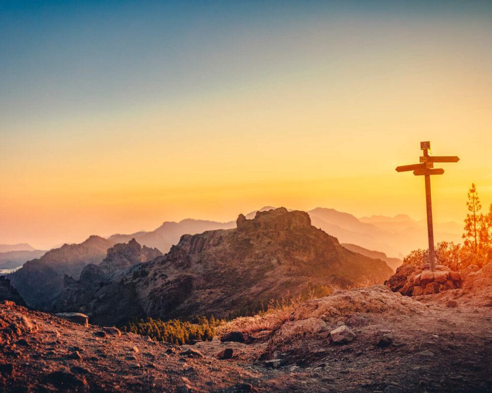 Wegweiser auf dem Gipfel des Roque Nublo im Licht des Sonnenuntergangs